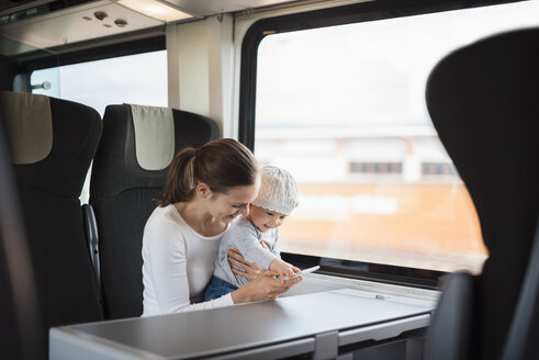 Mother with baby girl traveling by train looking on cell phone - DIGF02872