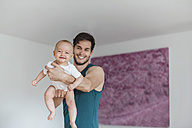 Father holding baby girl at home - DIGF02893