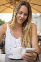 Young woman in a street cafe checking her cell phone - JUNF00917