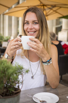 Portrait of smiling young woman in a street cafe - JUNF00920