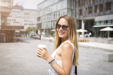 Smiling young woman holding takeaway coffee in the city - JUNF00923