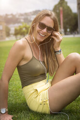 Happy young woman with earphones relaxing on lawn in park - JUNF00926