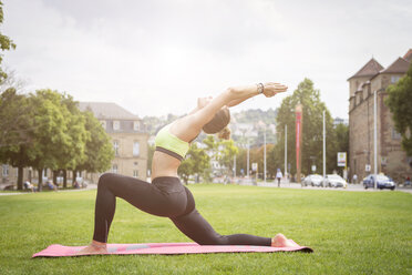 Young woman practicing yoga in a park in the city - JUNF00929