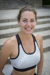 Portrait of smiling young woman during workout in the city - JUNF00935