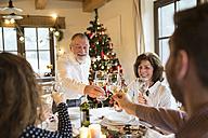 Senior man clinking glasses with family at Christmas dinner - HAPF02184