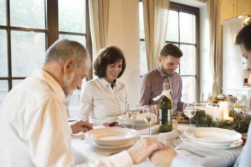 Family praying before Christmas dinner - HAPF02187