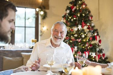 Smiling senior man looking at adult son at Christmas dinner table - HAPF02193