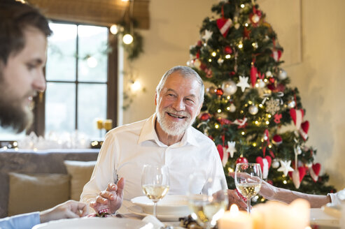 Smiling senior man looking at adult son at Christmas dinner table - HAPF02193