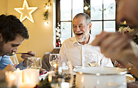Happy senior man looking at adult son at Christmas dinner table - HAPF02199