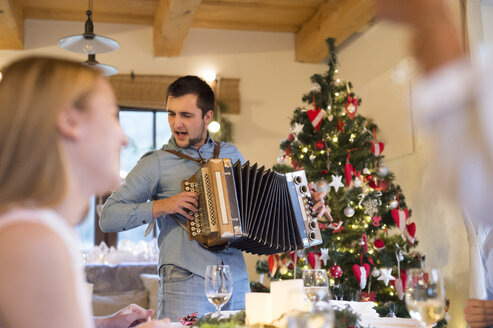 Young man playing accordion at Christmas dinner table - HAPF02205