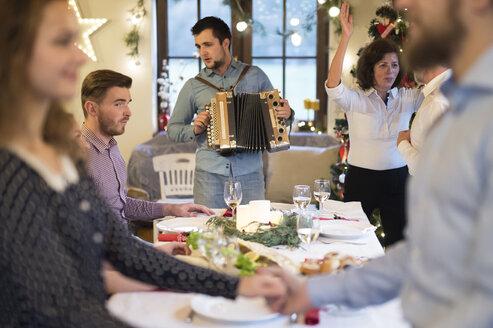 Young man playing accordion for family at Christmas - HAPF02211