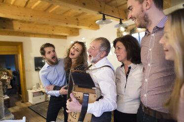 Senior man playing accordion for happy family - HAPF02214