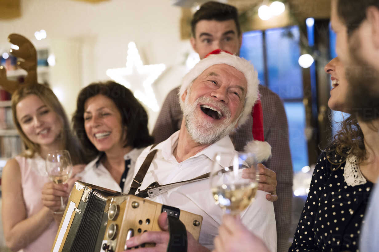 Senior man playing accordion for happy family at Christmas - HAPF02217 - HalfPoint/Westend61