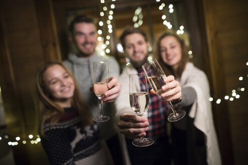 Happy friends holding champagne glasses outdoors at night - HAPF02220