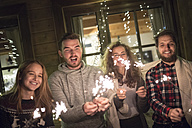 Happy friends holding sparklers outdoors at night - HAPF02223