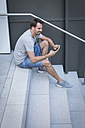 Man sitting on stairs, using smartphone - JUNF00940