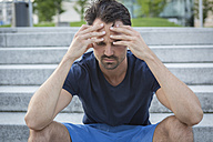 Athlete sitting on stairs with hands on head, having a headache - JUNF00976