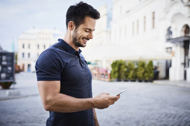 Smiling man using cell phone in the city - BSZF00075