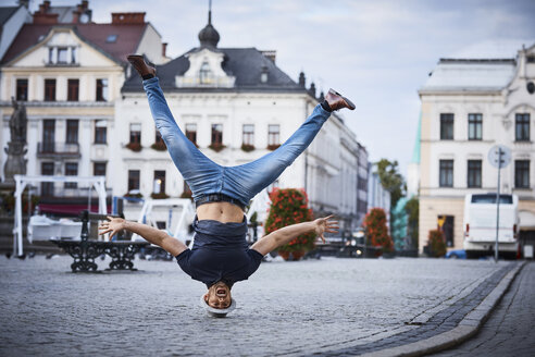 Man having fun doing headstand on square in the city - BSZF00078
