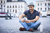 Man sitting on city square using phone - BSZF00081