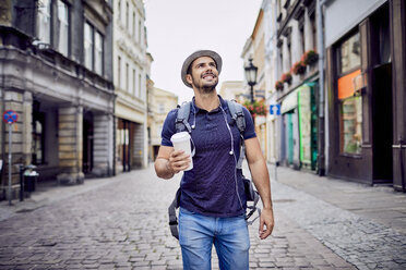 Traveler with backpack walking down city street and holding coffe - BSZF00084