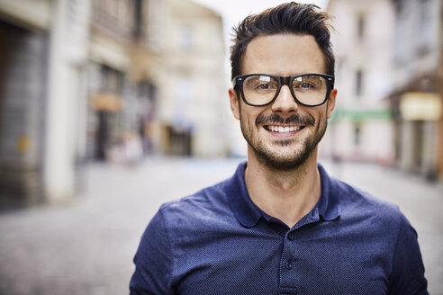 Portrait of smiling man with glasses in the city - BSZF00087
