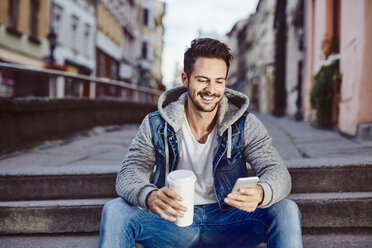Man with coffee sitting on stairs in the city using phone - BSZF00090
