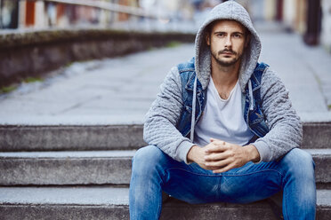 Serious man in hooded jacket sitting on stairs - BSZF00093