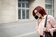 Young businesswoman in the city talking on the phone - JUNF00990