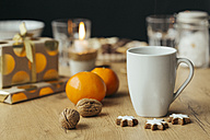 Cup of tea, tangerines, walnuts,  cinnamon stars and Christmas presents in the background - JHAF00005