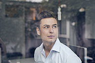 Young businessman behind glass pane in office - PNEF00171