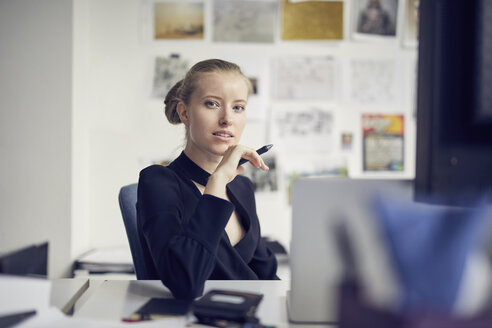 Portrait of young businesswoman at desk in the office - PNEF00177