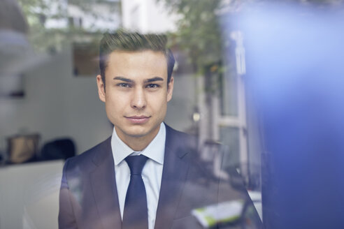 Young businessman behind glass pane in office - PNEF00180