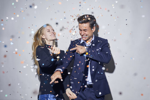 Two young businesspeople dancing under shower of confetti - PNEF00183