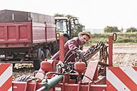 Farmer on field examining farm machine - UUF11926