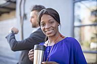 Portrait of smiling businesswoman with coffee mug and businessman in background - ZEF14652
