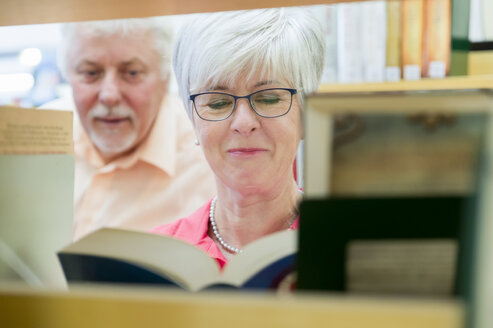 Portrait of smiling senior woman with  book in a city library - FRF00574