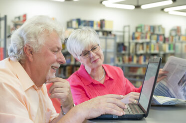 Senior couple with laptop and newspaper in a city library - FRF00577