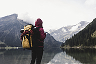 Austria, Tyrol, Alps, hiker standing at mountain lake - UUF11946