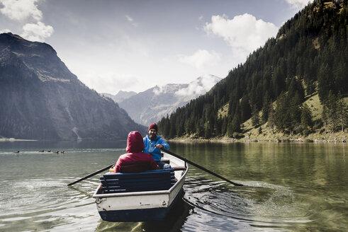 Austria, Tyrol, Alps, couple in rowing boat on mountain lake - UUF11955