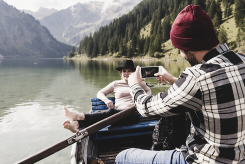Austria, Tyrol, Alps, man taking cell phone picture of woman in rowing boat on mountain lake - UUF11958