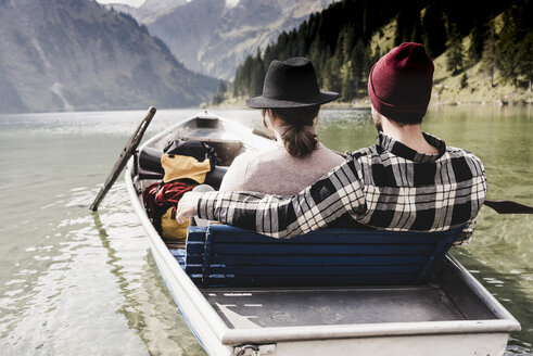 Austria, Tyrol, Alps, relaxed couple in rowing boat on mountain lake - UUF11961