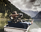 Austria, Tyrol, Alps, relaxed man in boat on mountain lake - UUF11964