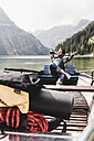 Austria, Tyrol, Alps, relaxed man in boat on mountain lake - UUF11967