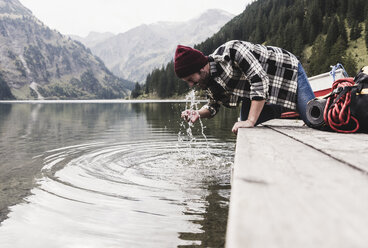Austria, Tyrol, Alps, man kneeling on jetty refreshing at mountain lake - UUF11973