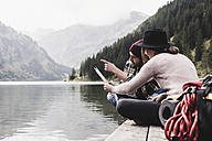 Austria, Tyrol, Alps, couple with map sitting on jetty at mountain lake - UUF11976