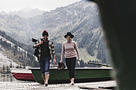 Austria, Tyrol, Alps, couple walking on jetty at mountain lake - UUF11982