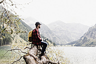 Austria, Tyrol, Alps, hiker sitting on tree trunk at mountain lake - UUF11991
