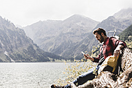 Austria, Tyrol, Alps, hiker relaxing on tree trunk at mountain lake checking cell phone - UUF11994