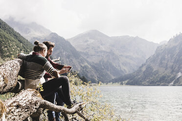 Austria, Tyrol, Alps, couple relaxing on tree trunk at mountain lake using cell phone - UUF11997